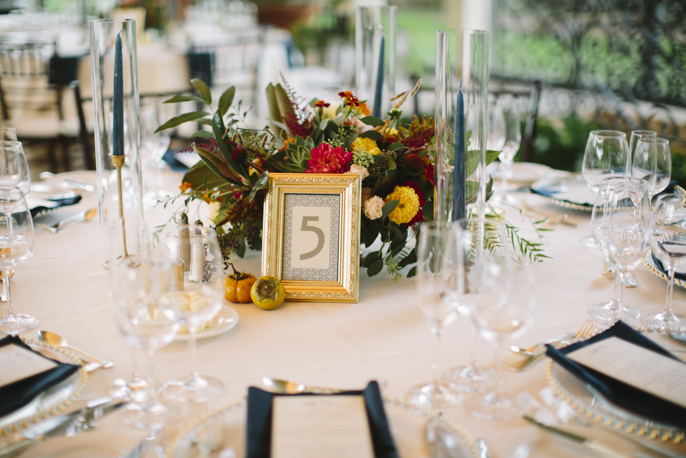 Emily's centerpieces were designed in brass compotes, and incuded persimmons, berries, succulents, dahlias, garden roses, foliage and magnolia leaves. Brass and pewter candlestick holders with navy taper candles finished the polished look.