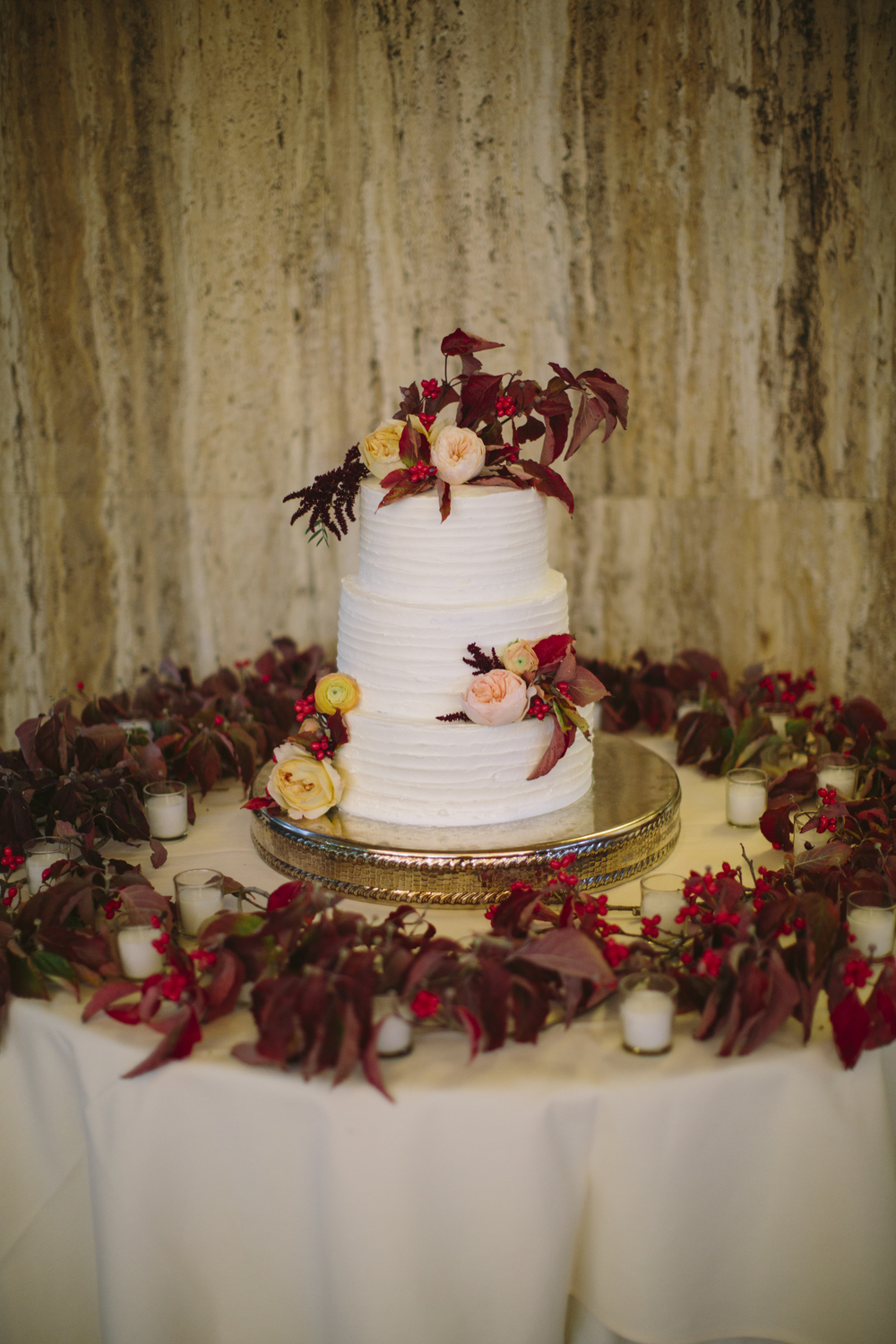These cake flowers were the finishing touches to a day filled with fall florals.  Yellow and pink roses, ranunculus, red berries, and deep red leaves decorated each layer and formed a garland for a truly seasonal look.