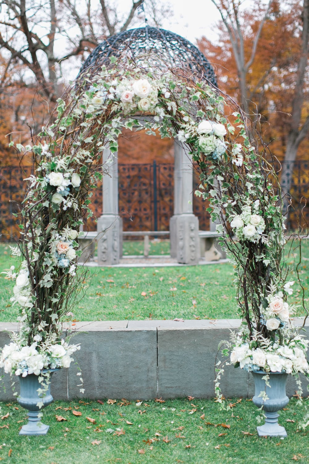 We used our large grey urns for the ceremony decor, connecting them with branches, and loose flowers to create an arch for the couple to stand under.  Roses, hydrangea and ivy helped soften the look of the curly willow.
