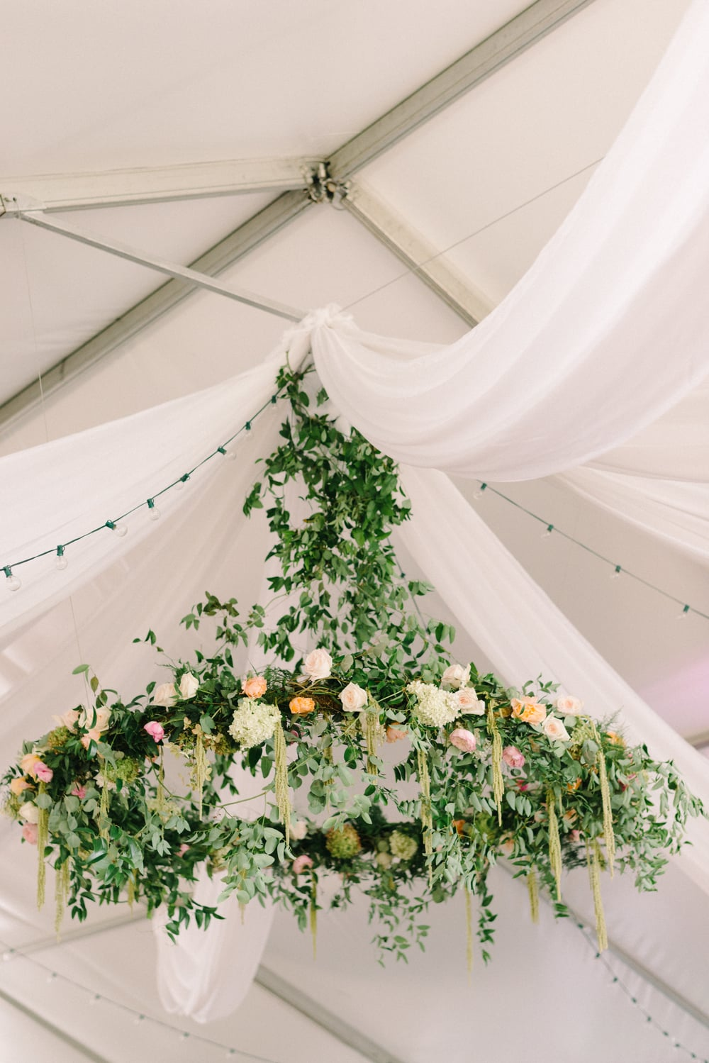This was our initiation into floral chandeliers and we were (and still are!) so proud of this design. We covered the base with moss before wrapping tons of smilax vine and greenery around the diameter. More hydrangea, roses and hanging amaranthus added color to this beautiful piece. The tent draping and lighting helped make this stand-out piece really shine.