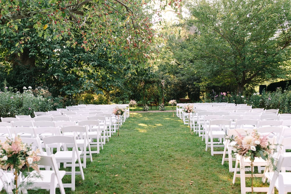 Alexandra and Andrew's ceremony space was breathtaking. The surrounding forestry provided an intimate setting, andAlexandra's father made this wooden arch for the couple to pronounce their vows underneath. We accented the arch with smilax vines and floral corner pieces of vines, greenery, roses, lisianthus and stock.