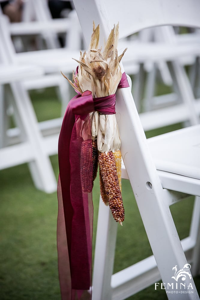 """Keeping up with Amanda and Harry's theme of """"FALLing in Love,"""" we added Indian corn as aisle arrangements, tied off with burgundy ribbon."""