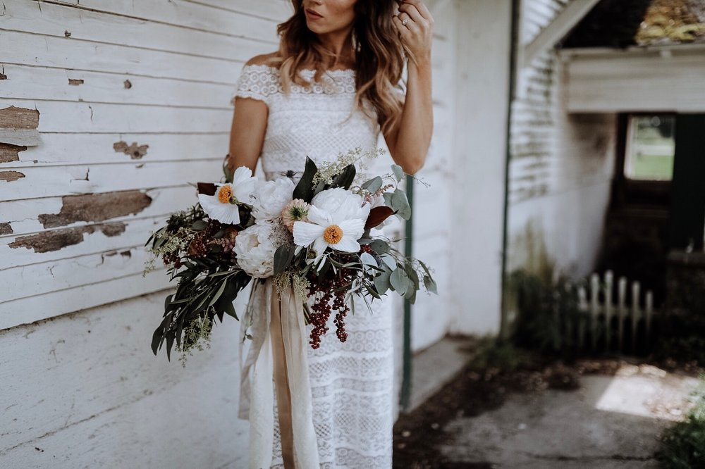 bohemian bride posing with bouquet