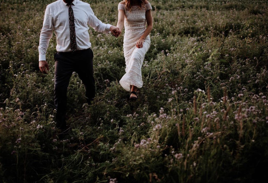 bride and groom strolling through field