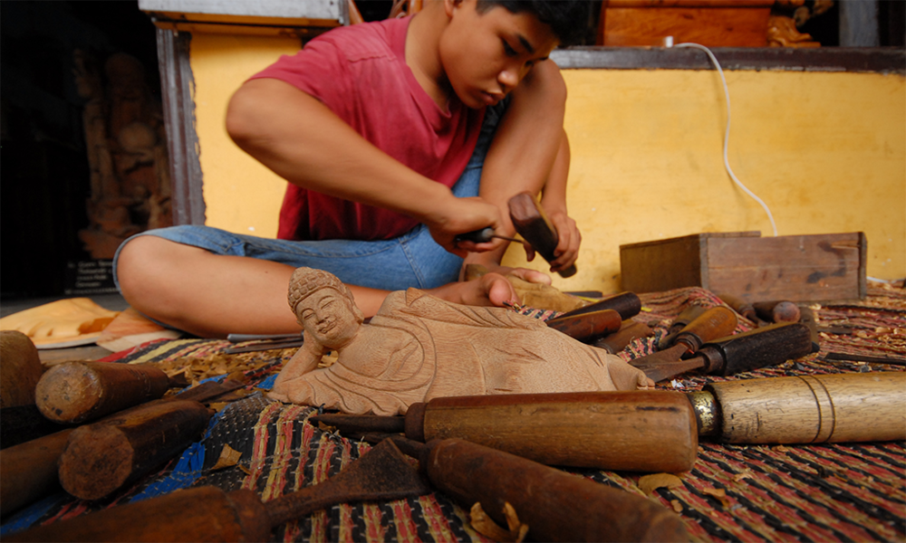 Fig. 3 A skilled artisan crafting a Buddha figure.