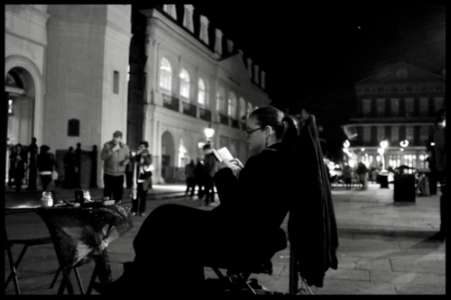 Reader in the shadows of St Louis Cathedral and Jackson Square, New Orleans. Credit: Kevin Rabalais