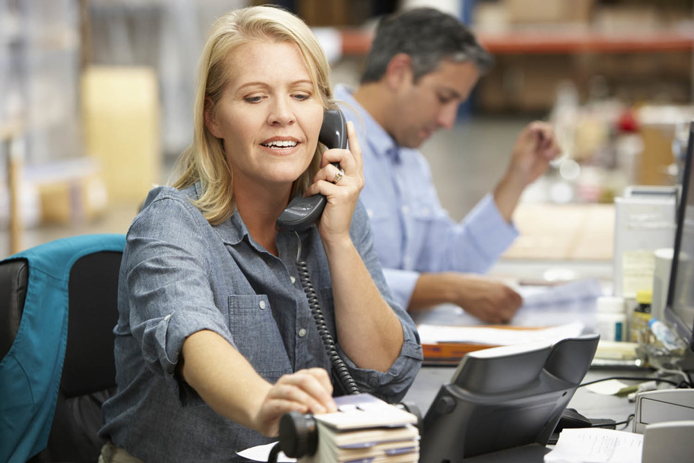 businesswoman-working-at-desk-in-warehouse-P3VGDRS.jpg
