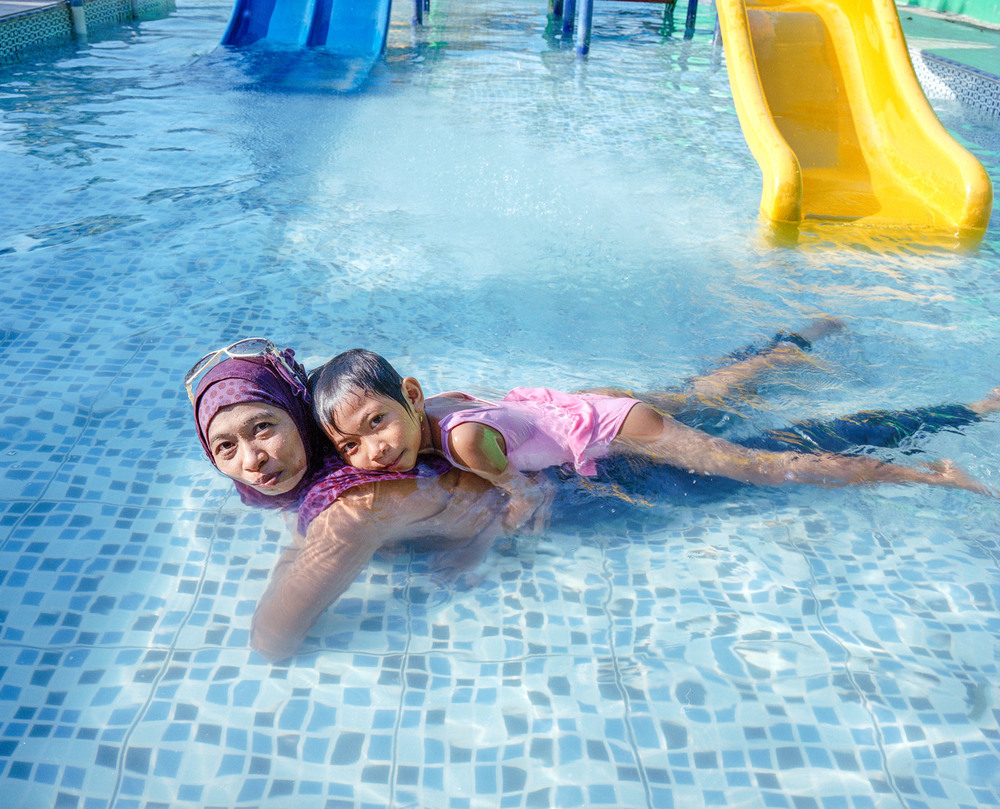 A portrait of Ibu Ratna and Amel at a water park.  They love to swim and play on the waterslide.