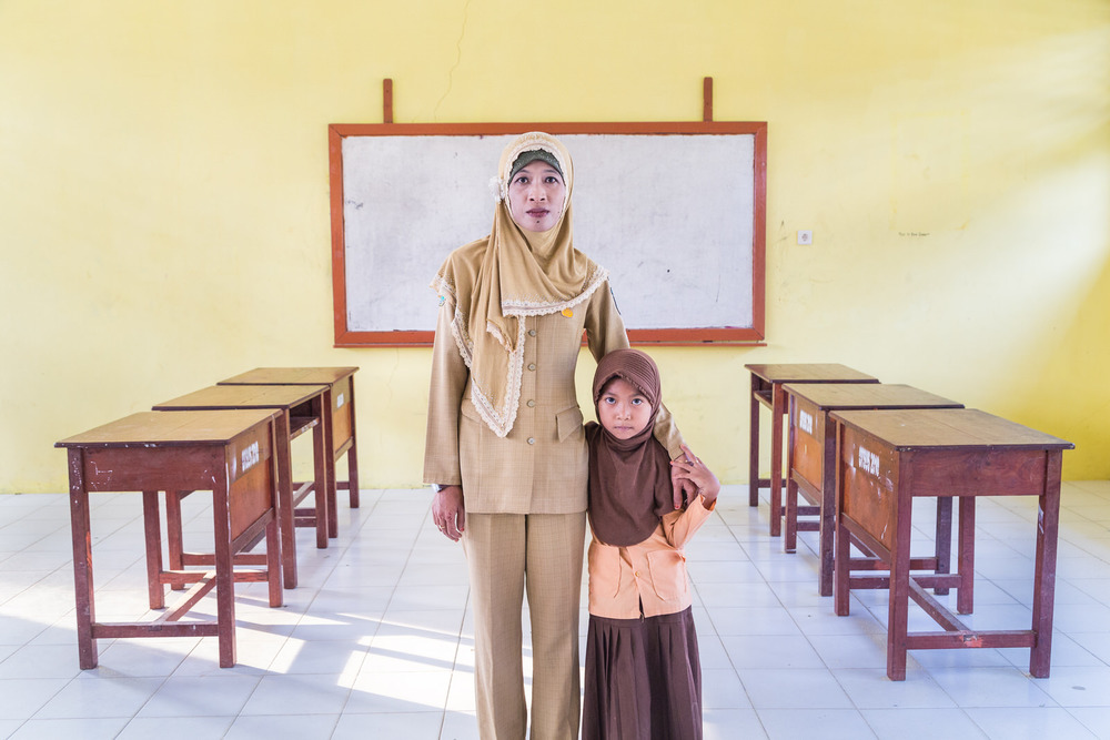 A portrait of Ibu Ratna and Amel inside her classroom.