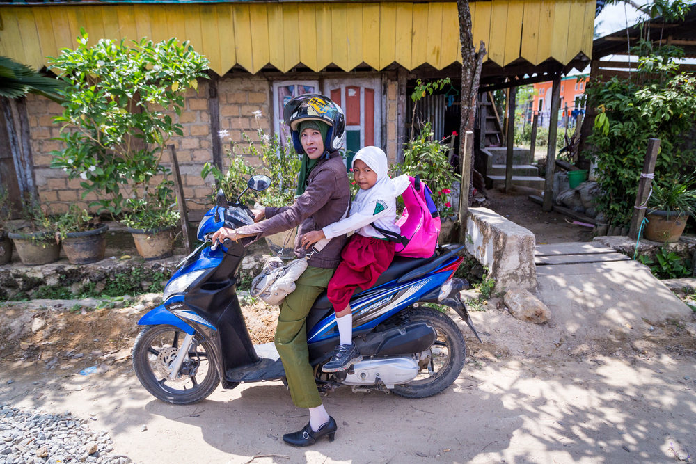 A single mother, Ibu Ratna takes her 7-year-old daughter, Amel, to school before going to work.