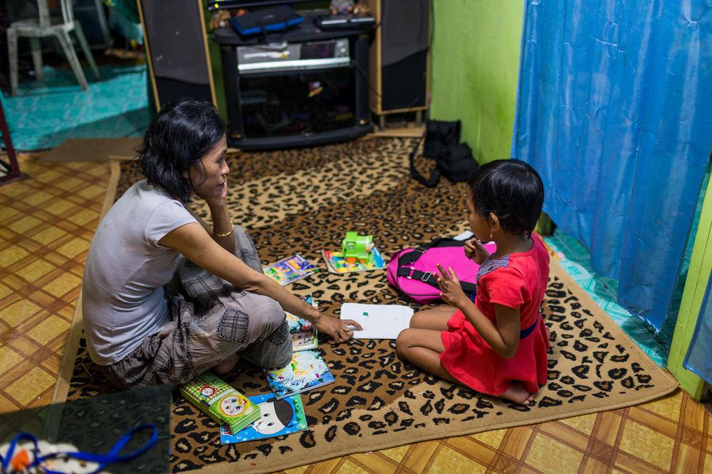 Ibu Ratna helps Amel with her homework.