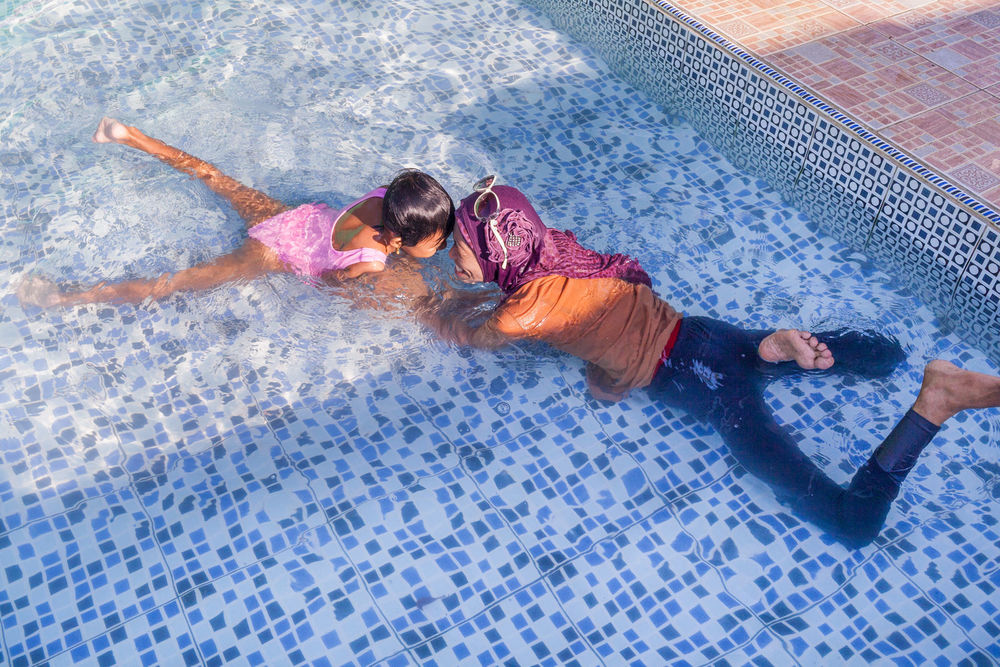 Ibu Ratna and Amel swim and play waterslide at a water park.