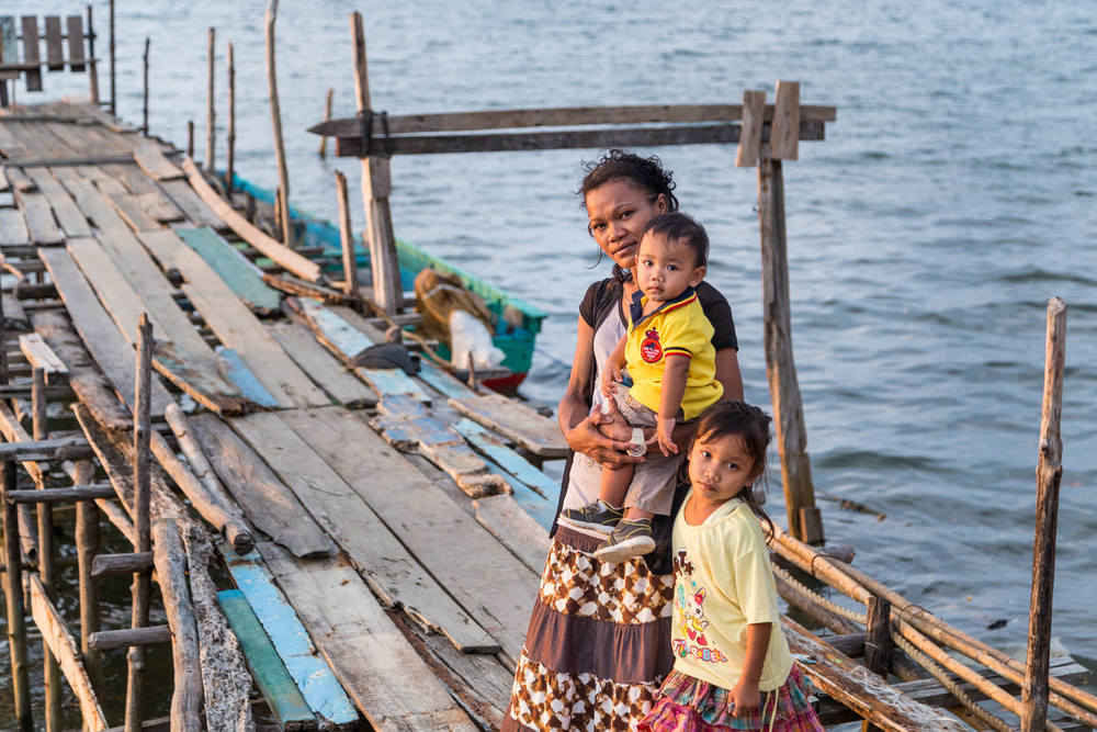 A portrait of Ibu Siti with Young and Vio on the dock near their house.