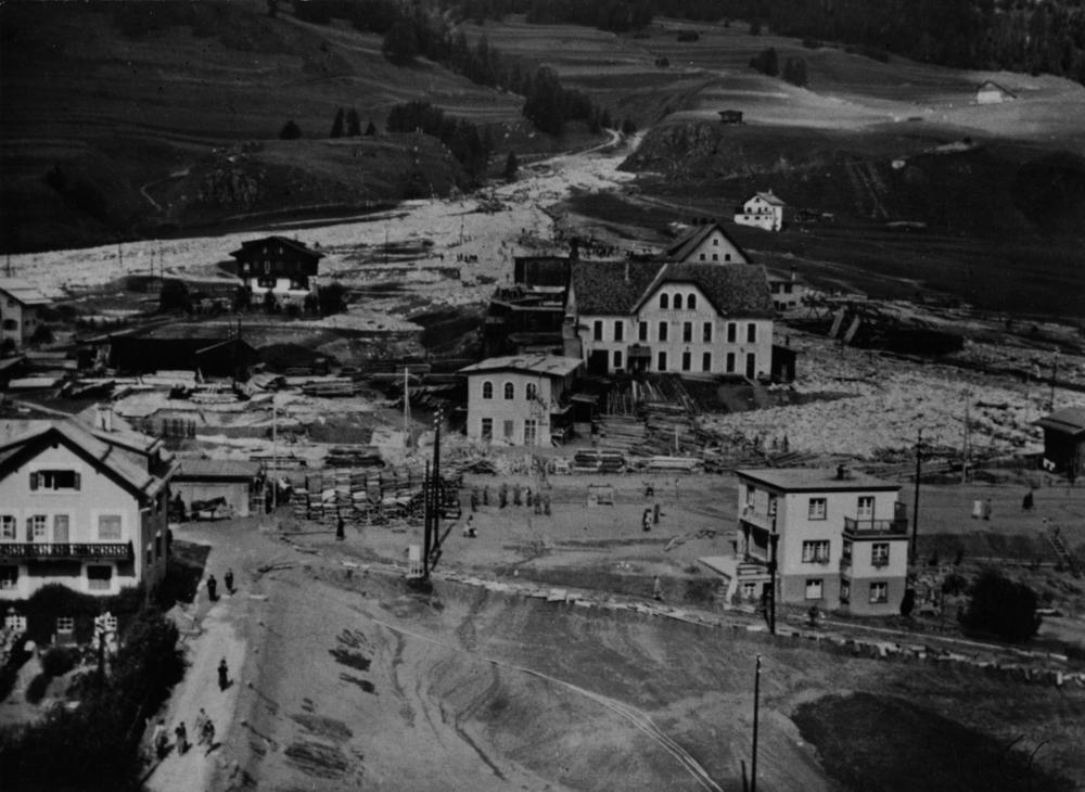 1. September 1944: Eine Rüfe richtet grossen Schaden an. Mitten im Schuttkegel die Chesa Akelei, unversehrt (im Bild links oben). Unterhalb davon, wo das Pferdefuhrwerk steht, der Bahnhof; das grosse Gebäude rechts der Mitte ist das Baugeschäft (Chaletfabrik) Celerina mit dem überschwemmten Holzlager (Blick bergwärts).