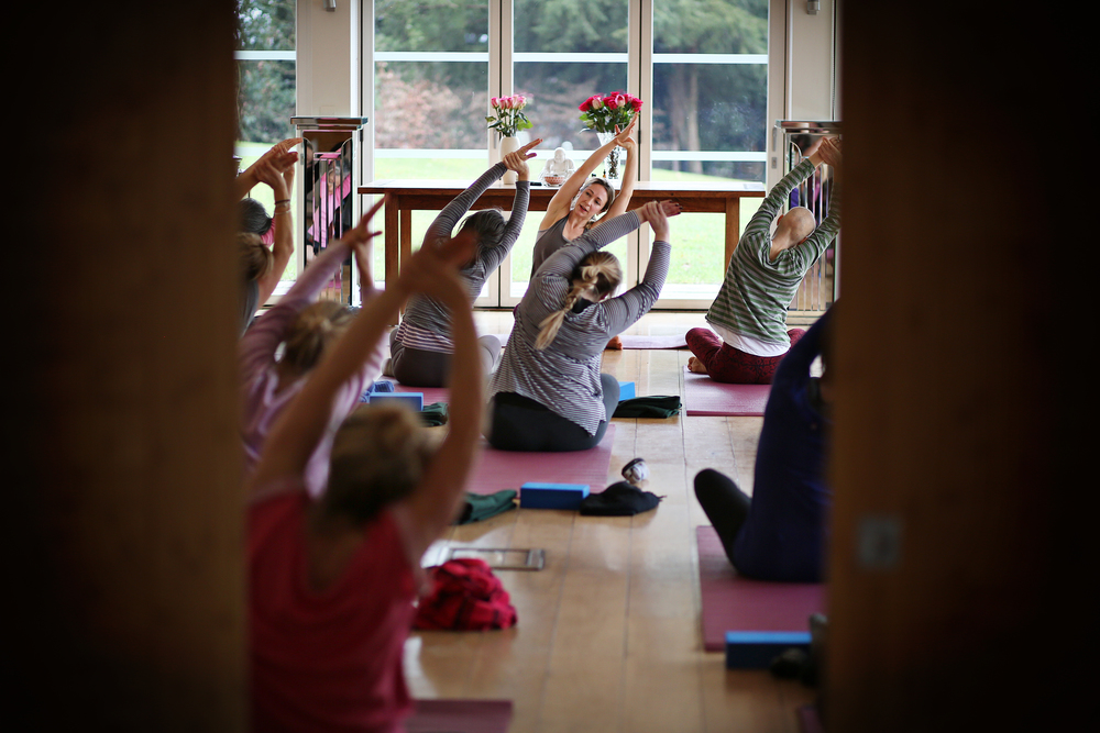 Jess Teaching Yoga Arm Stretch pose to group.jpg