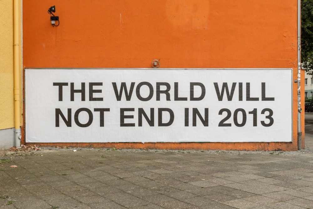 The World Will Not End  as a billboard on the outside wall of the building that houses the Wand Gallery in Moabit, Berlin, Germany facing the Justizvollzugsanstalt prison, the most central prison in Berlin. In collaboration with Claus Philipp Lehmann. Inkjet print wallpaper. Font: Helvetica. Part of 'The Oracle' exhibition curated by Melissa Steckbauer and Mathilde ter Heijne of ƒƒ
