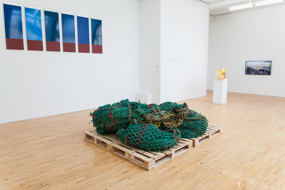 Installation view. Part of the 12 paintings, the net heap, the 'Goldship' sculpture, the inscription from Allan Sekula and the video 'Material Puffin' on a loop on the flatscreen monitor. Photo: Dennis Helm