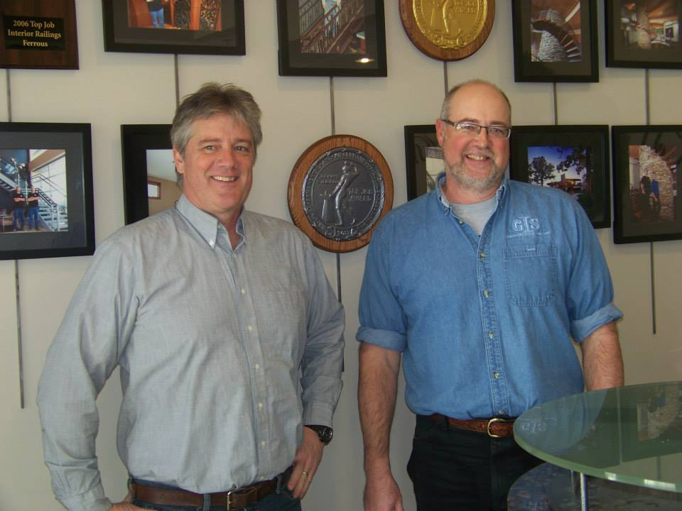 Owners Ken and Dave Gutbrod stand next to one of the bronze metals given to Germantown Iron & Steel from the National Ornamental & Miscellaneous Metals Association (NOMMA). Germantown Iron & Steel had received two gold (06' and 12') and one bronze (04') Top Job Awards from NOMMA.