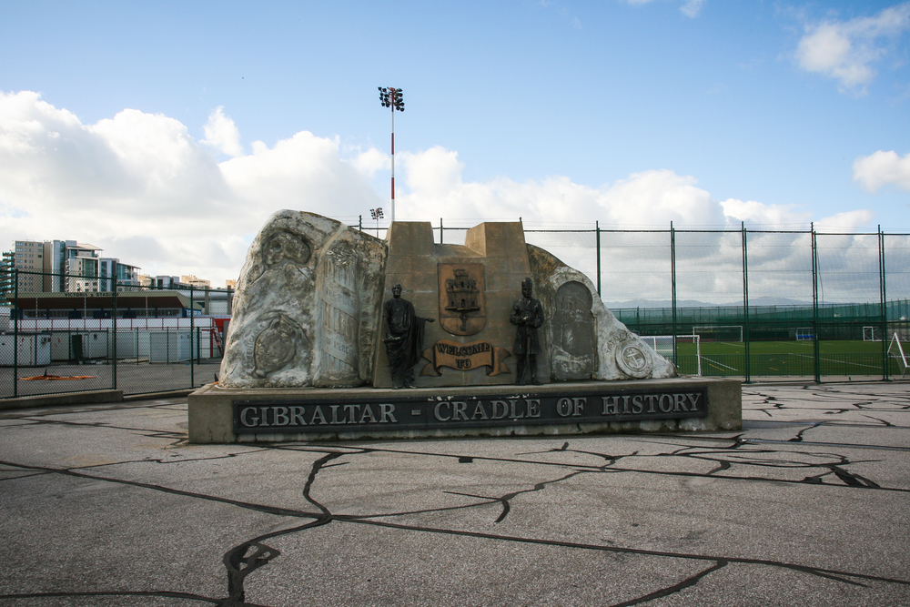 Gibraltar . The Cradle of History Monument. Behind it: the few Gibraltar soccer stadiums which are just a few feet from the airport runway.