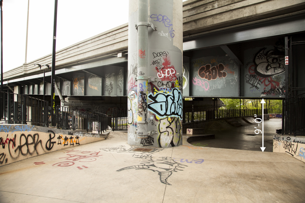 "Highway underpass leading to the remaining portion of the skatepark. The overall head height of this space is 9'-0"" at the lowest point. While the park continuously slopes downward toward the river, the clearance beneath the highway underpass doesn't go beyond 12'-0."" While the proximity to the highway and its constant noise and vibrations would be problematic for a building, the skate park, which is generally loud and messy in nature, thrives in these conditions. It has become a blank canvas for art and exploration of skating, rollerblading, and biking."