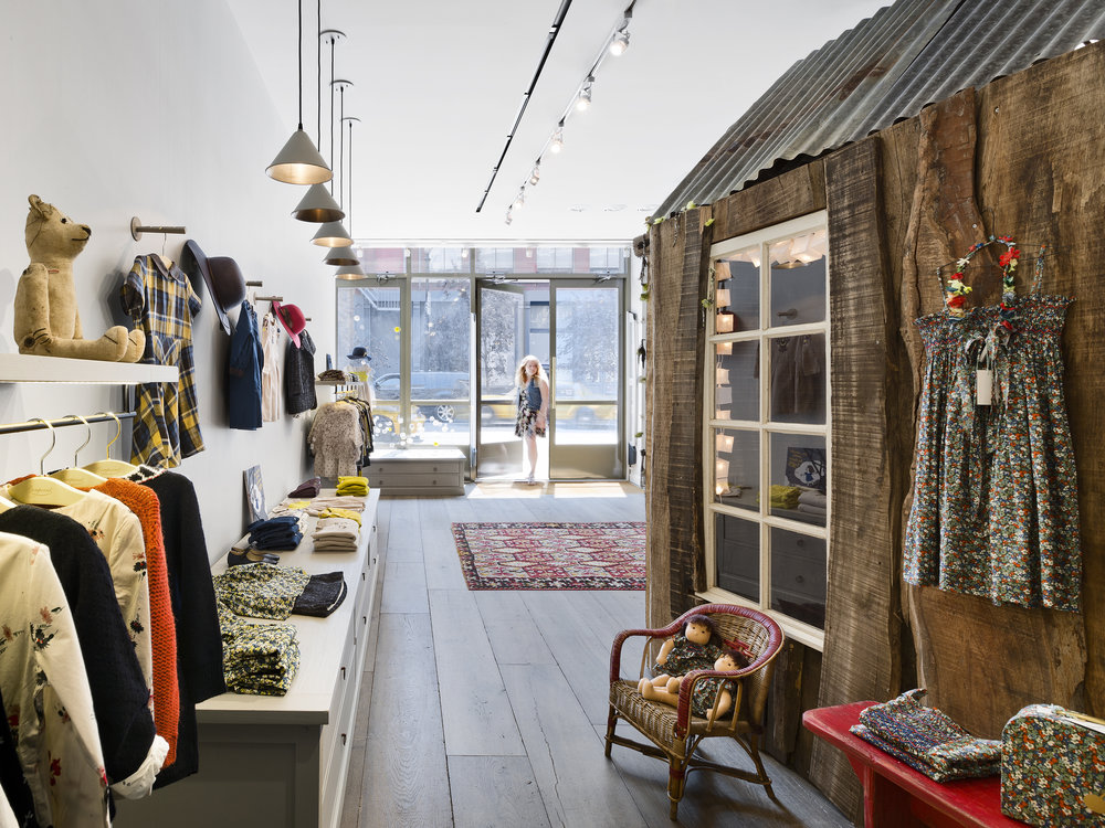The hygge-based design in the Bonpoint children's clothing store in Manhattan creates an oasis of calm and comfort with naturally fi nished wood for furnishings, a children's playhouse, and a small seating area adorned with comfortable couches and pillows. Photo: Alexander Severin.
