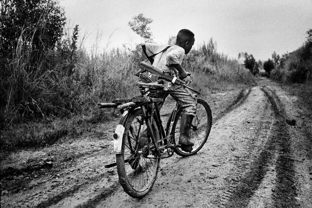 A child soldier rides back to his base in Ituri district, northeastern Congo. 2003.  Inquire about this image