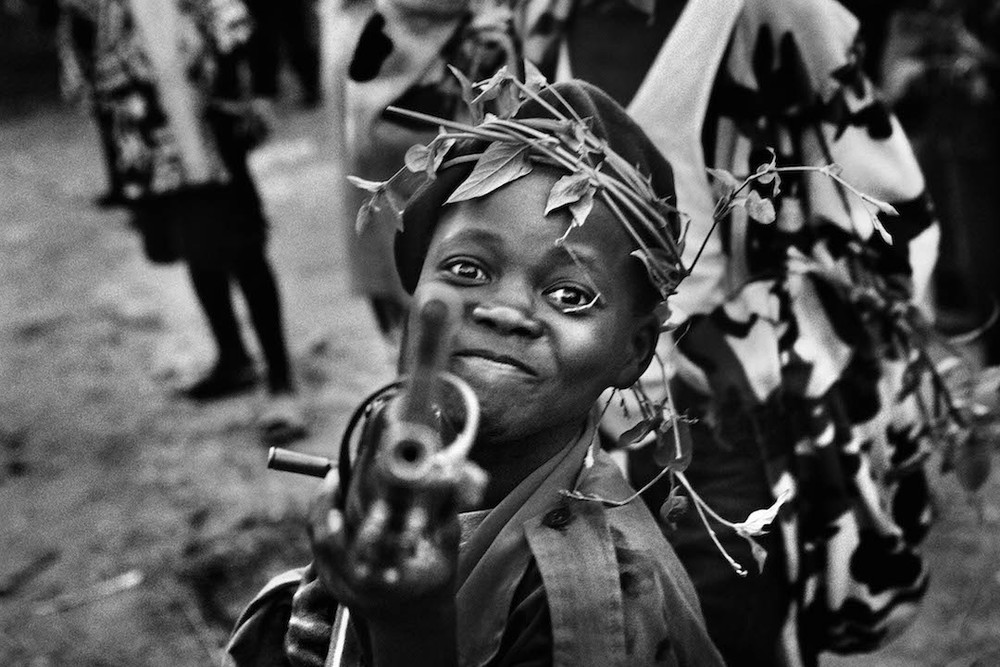 A child soldier with the Mayi-Mayi militia waits in Kanyabyonga as CNDP rebels advance. He was recruited while young men in the area were being abducted by the rebel forces. He didn't want to be forced to fight, so he volunteered with the Mayi-Mayi. 2008.  Inquire about this image