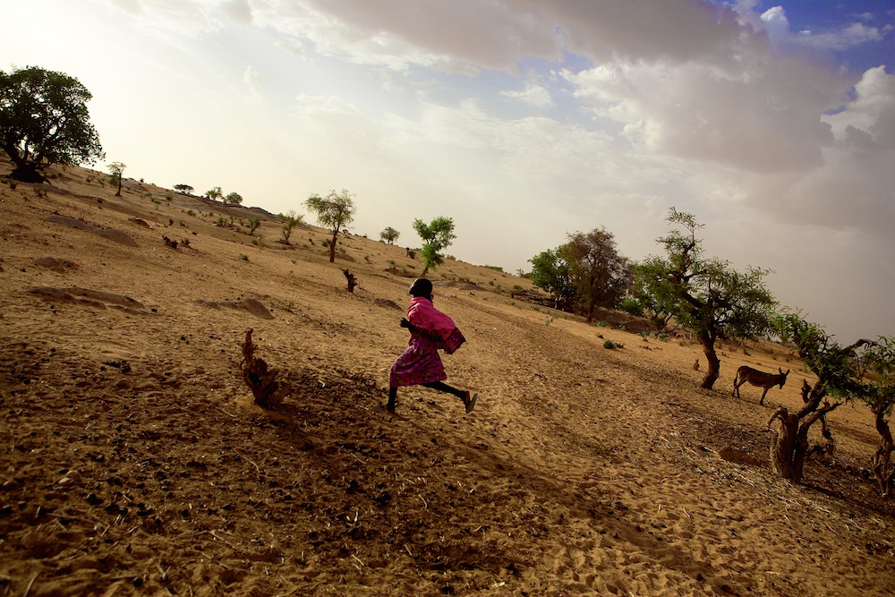 A young girl runs through a displacement camp in Darfur. Sundan, 2005.  Inquire about this image