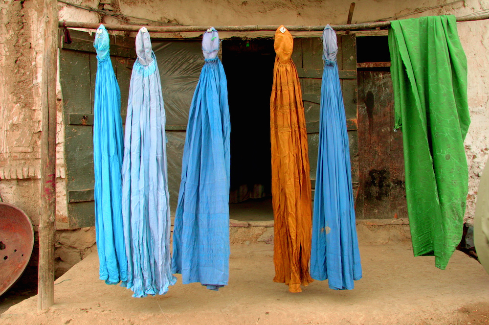 Burqas dry on a street in Kabul shortly after the overthrow of the Taliban.  Afghanistan, 2001  Inquire about this image