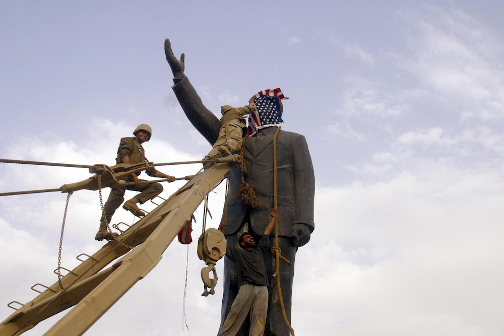 A U.S. Marine covers the face of a statue of Saddam Hussein with a U.S. flag before the statue was toppled in Baghdad, April 9, 2003.   Inquire about this image