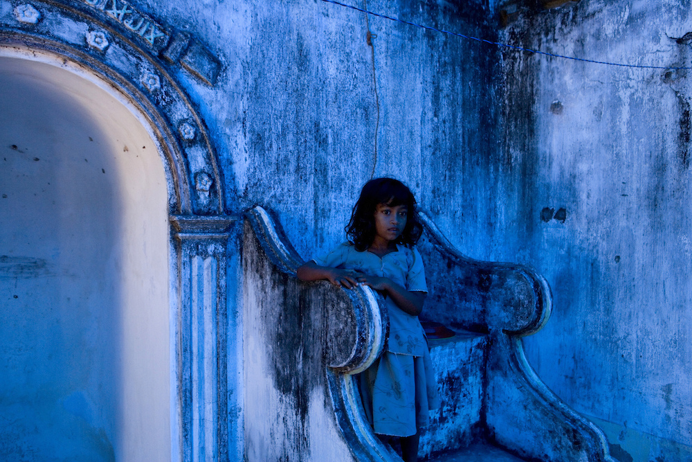 A displaced Muslim girl takes up shelter at a destroyed mosque after fleeing a government offensive against the Tamil Tigers. Many civilians were killed and wounded, and thousands were displaced as a result.  Sri Lanka, 2007   Inquire about this image