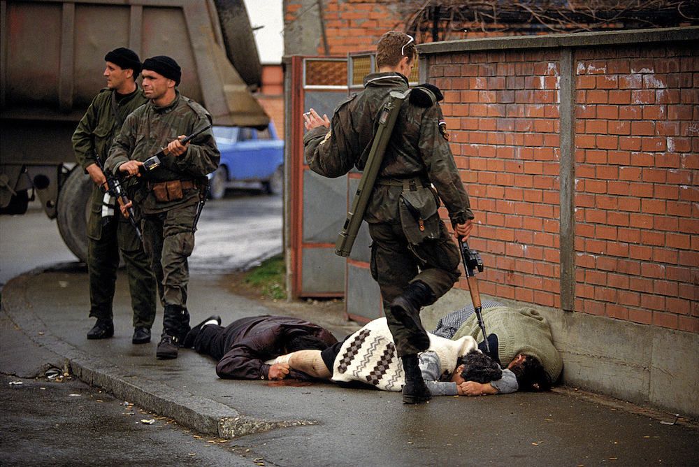 Members of Arkan's Serbian paramilitary group, the Tigers, execute unarmed Bosnian muslim civilians during the first battle of the Bosnian war. 1992  Inquire about this image
