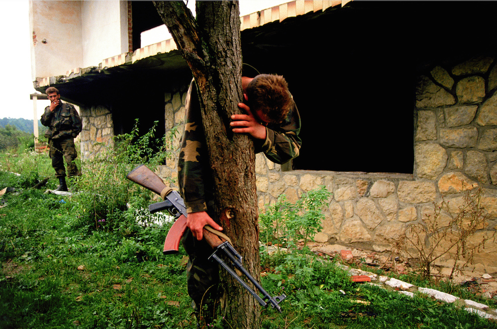 A Bosnian Muslim soldier collapses in grief in the front yard of his destroyed home. It was alleged that over 60 people, killed by Serbian forces, were buried in the front yard. Bosnia, 1995  Inquire about this image