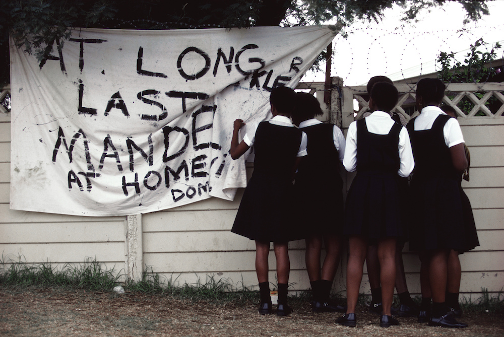 Young girls wait outside the home of Nelson Mandela the day after his release from prison after serving 27 years. South Africa, 1990.  Inquire about this image