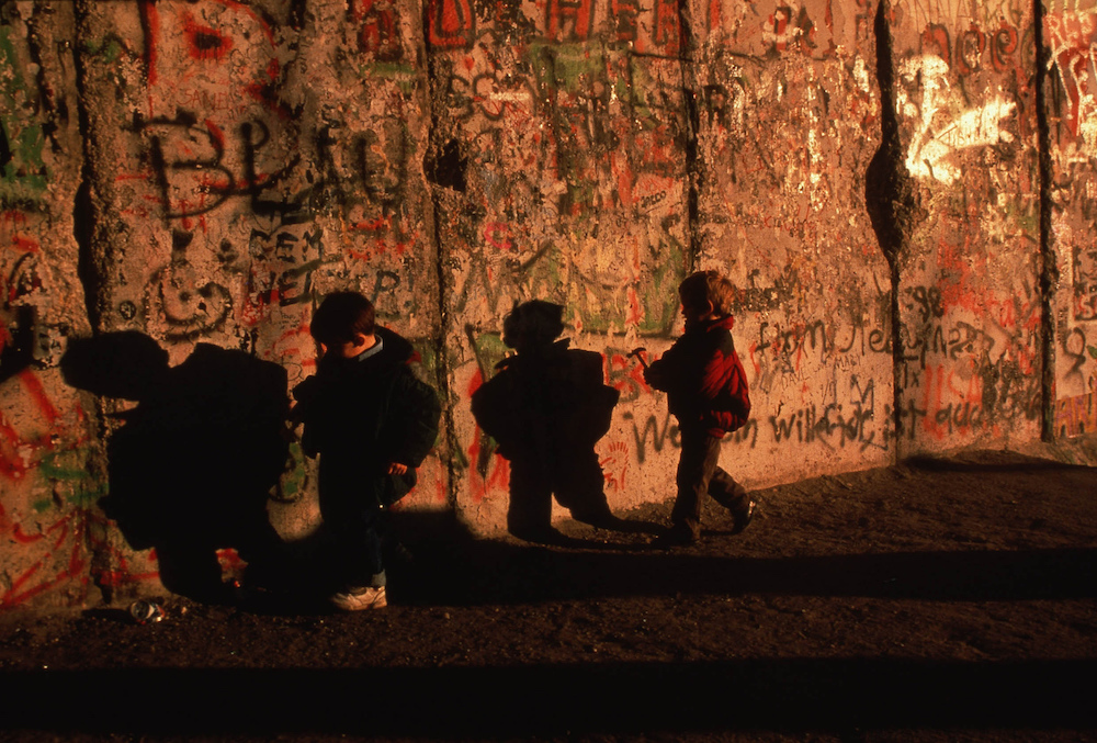 German children run alongside the Berlin wall as the wall came down and reunified East and West Germany. Germany, 1989  Inquire about this image