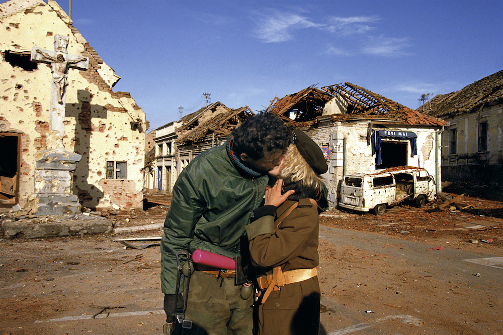 A Serbian couple kisses after the fall of Vukovar. The city was under siege for 3 months. Croatia, 1991  Inquire about this image