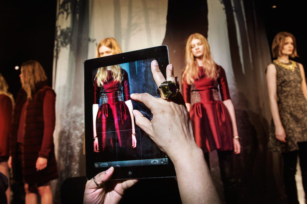 A guest takes an iPad photo of the models during the ADEAM presentation at Lincoln Center. Mercedes-Benz Fashion Week, New York City, Fall 2013.  Inquire about this image