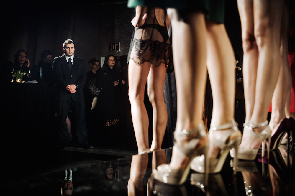 A security guard looks at the models during La Perla's presentation at the Dream Hotel.  Mercedes-Benz Fashion Week, New York City, Spring 2014.  Inquire about this image