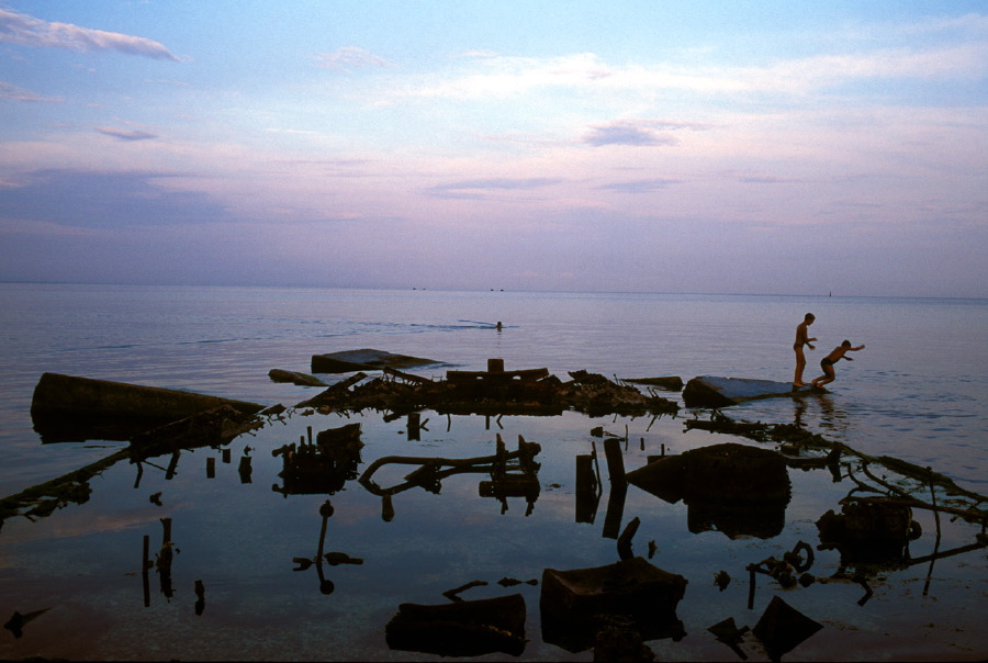 A scene at dusk along the waterfront of Feodosia is dominated by the remains of the rusted out hull of a ship that local kids play on. Feodosia, Crimea, 1993.  Inquire about this image