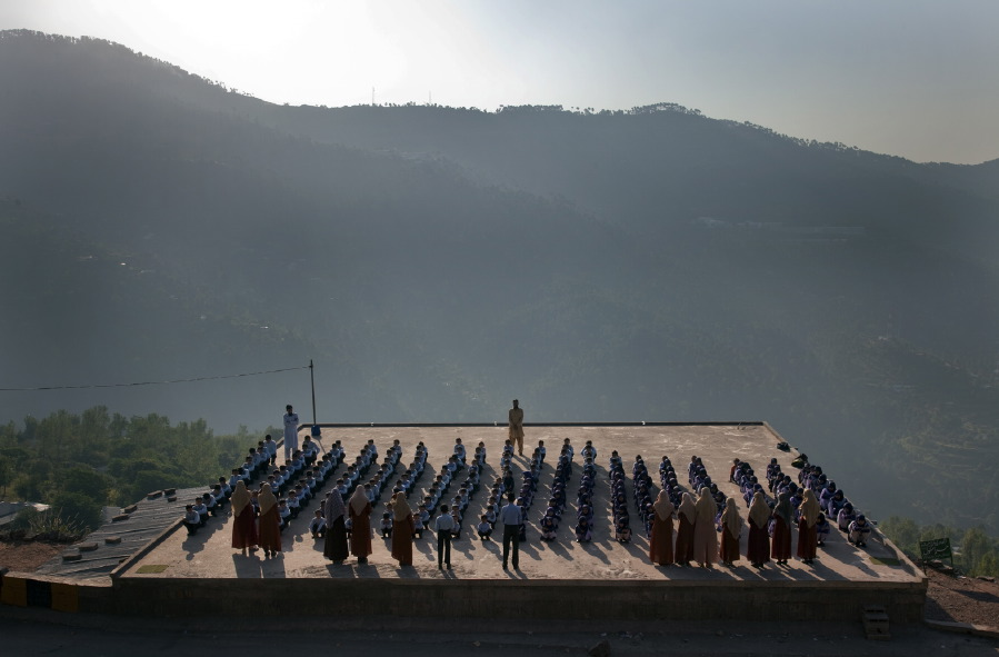 "Just outside the hill town of Muree, in the foothills of the Himalayas and overlooking Islamabad and Rawalpindi, students line up on the roof of the Hira School, a privately run religious school with the motto, ""Education in Koran and Computer, side by side."" Pakistan, December 2009.  Inquire about this image"
