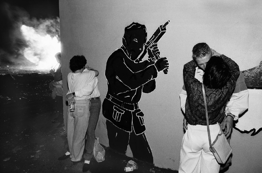Protestant youth kiss under a paramilitary mural in a working class housing estate in Belfast, Northern Ireland. July 1989.   Inquire about this image