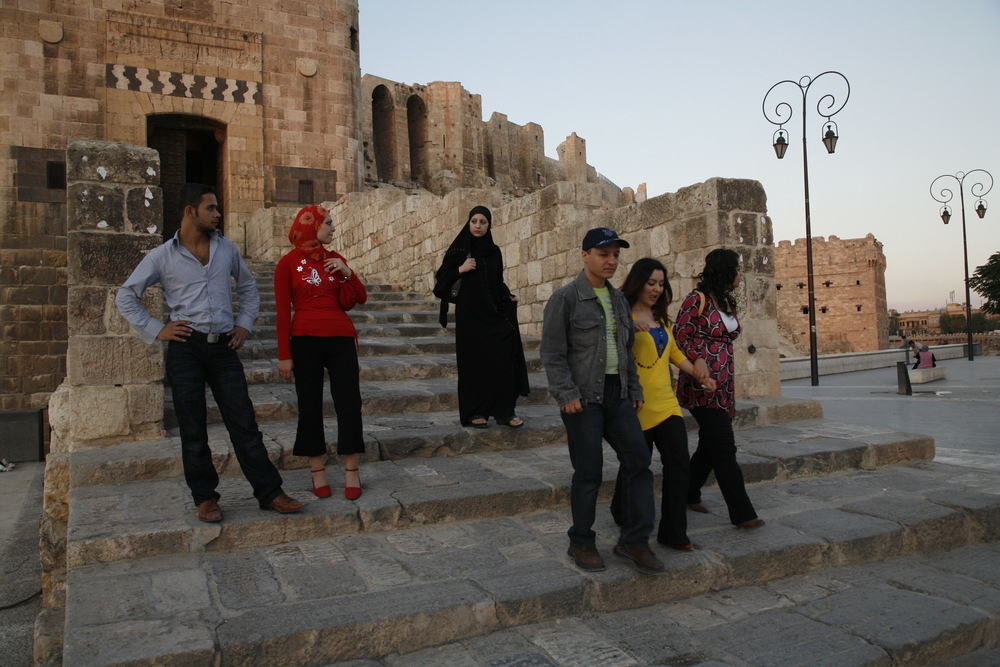 Young Syrians of different traditions pass each other on the steps of Aleppo's Citadel. Syria, October 2008.  Inquire about this image