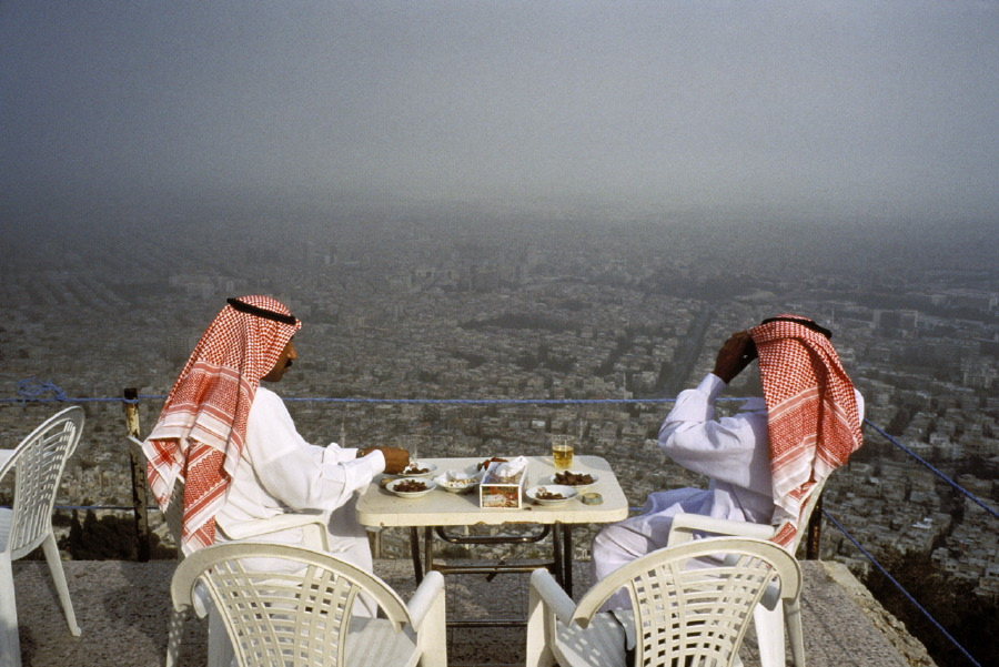 Saudi tourists take in the sights overlooking Damascus and drink beer at a cafe on Mt. Kassion. Syria, May 1995.  Inquire about this image