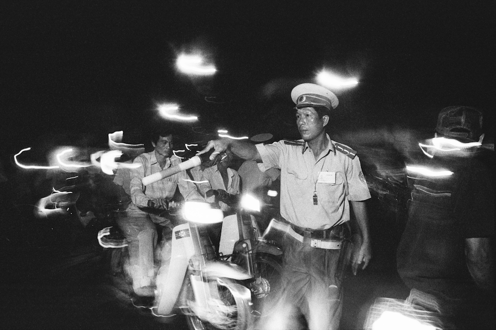 Saigon's traffic police, always unflappable, are having to adapt to the massive increase of motorbike traffic in the city, cause of terrible smog and congestion. 1994.   Inquire about this image