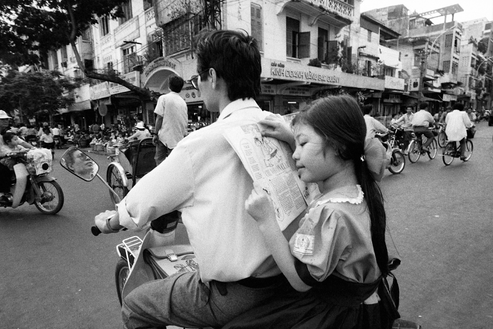 A father's back makes a comfortable reading stand for this girl on her way to school in Cholon, the Chinese district of Saigon. 1994.  Inquire about this image