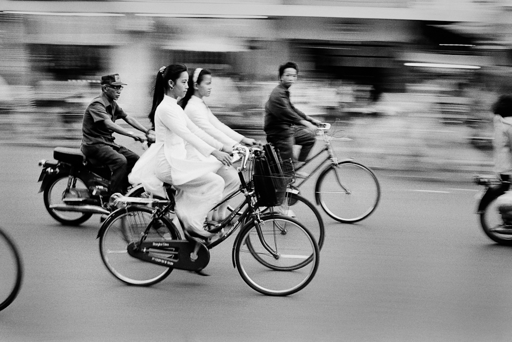 The A.M. commute; schoolgirls dressed in traditional ao dai a pre-communist fashion making a comeback since the late 1980's. Saigon, Vietnam. 1994.  Inquire about this image