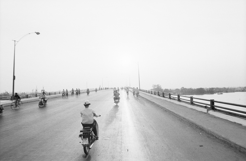Crossing the American-built bridge that spans the Saigon River, which heads east to cleaner air and open spaces beyond the city limits. 1994.  Inquire about this image