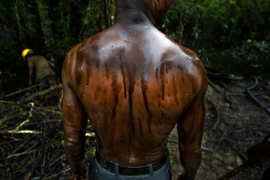 A worker cleans an oil spill from an abandoned Shell Petroleum Development Company well in Oloibiri, Niger Delta. Nigeria, July 2004.  Inquire about this image