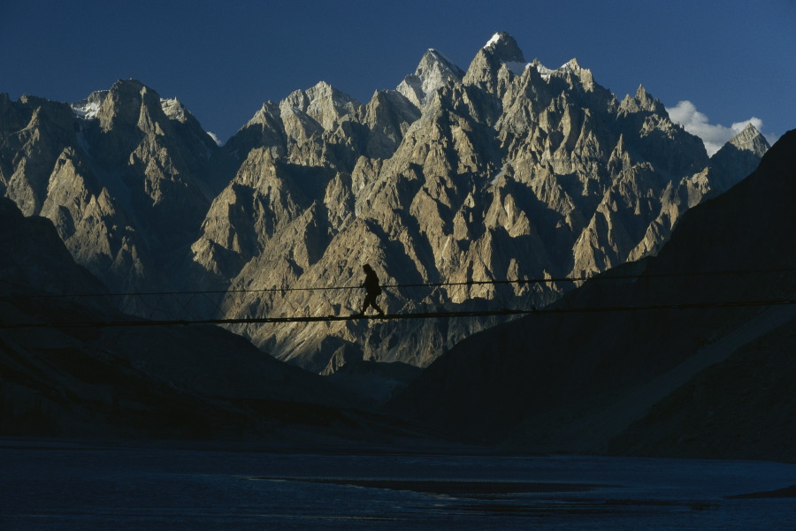 A lone woman crosses the Hunza River in Gulmit, Pakistan with Cathedral Mountain and the Karakoram Range providing otherworldly scenery. September 1997.  Inquire about this image