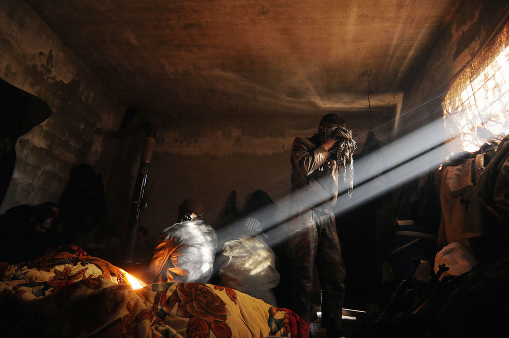 March 18, 2012: Near Al Janoudia, Syria. Rebels are drinking tea and washing up early in the morning inside their makeshift defensive position.  Inquire about this image